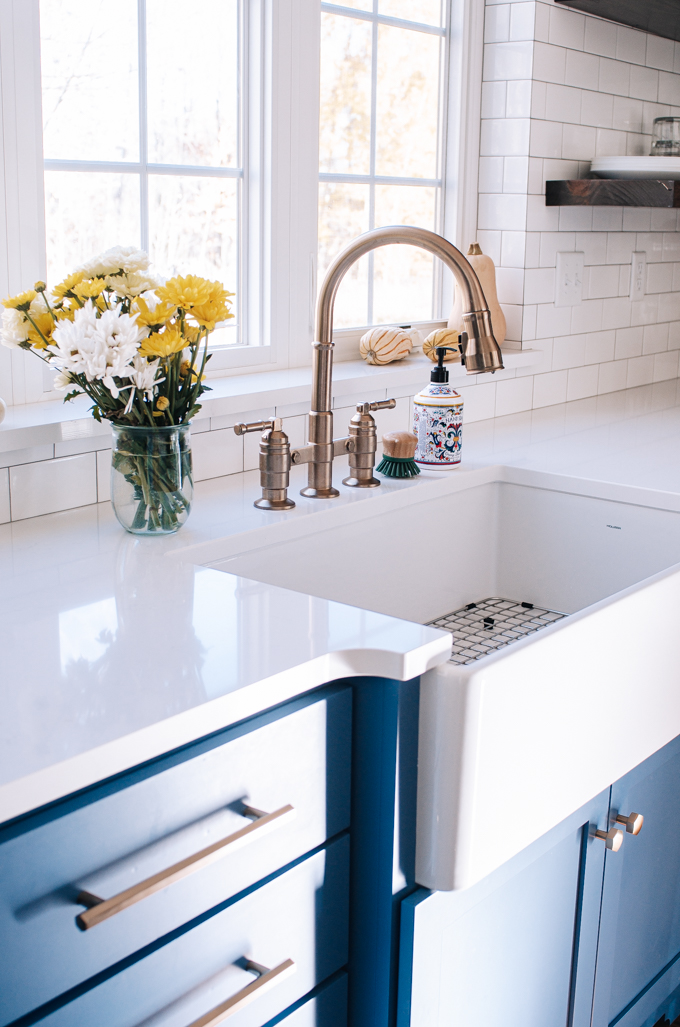 White apron front sink in front of window with bronze/gold bridge faucet in a transitional modern farmhouse kitchen.