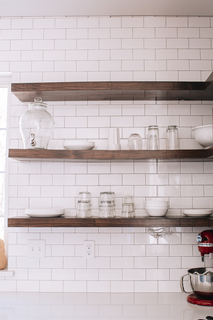 Open shelving in a transitional industrial modern farmhouse kitchen with subway tile backsplash up to the ceiling.