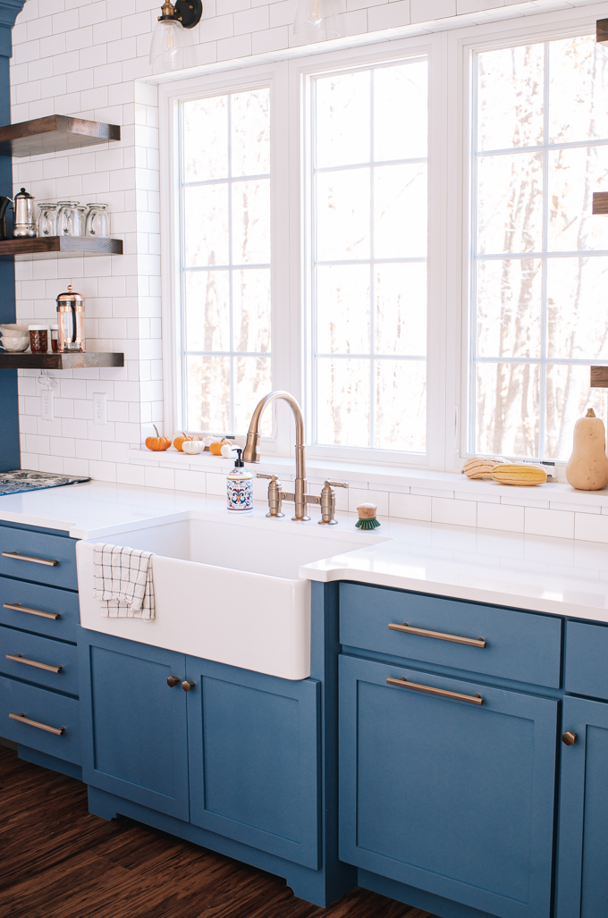 White apron front sink with a pull out bridge faucet in front of windows.