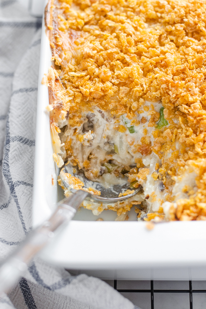 The baked gluten free cheesy potatoes (AKA funeral potatoes) in a white casserole dish on top of a wire cooling rack with a scoop taken out.