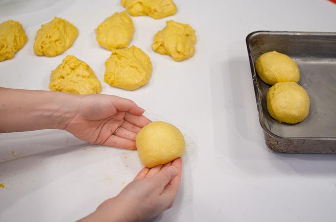Shaping the pumpkin sourdough dinner rolls into balls.