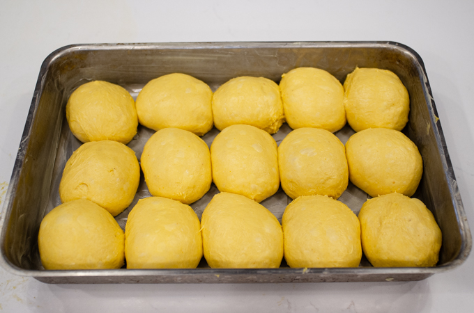 Placing the shaped dough balls in a greased 13x9 inch pan.