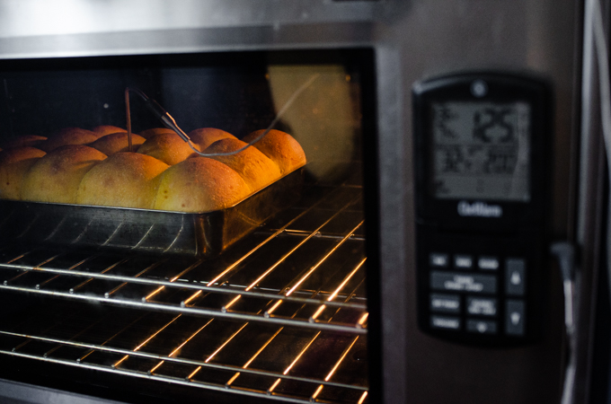 Baking the pumpkin sourdough dinner rolls with a probe thermometer.
