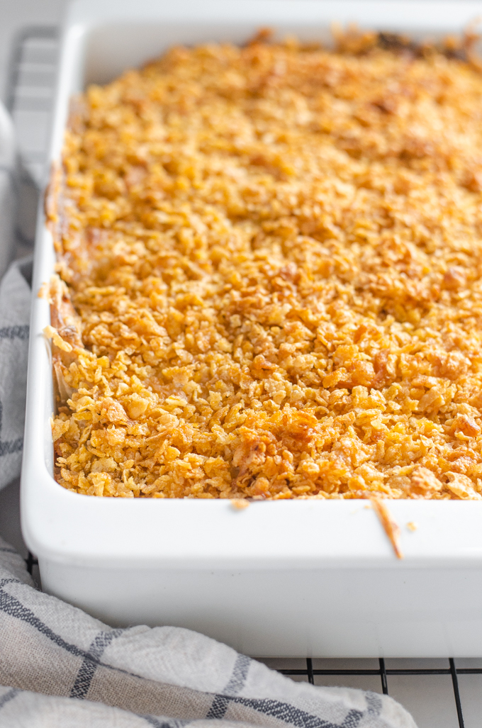 The baked gluten free cheesy potatoes (AKA funeral potatoes) in a white casserole dish on top of a wire cooling rack.