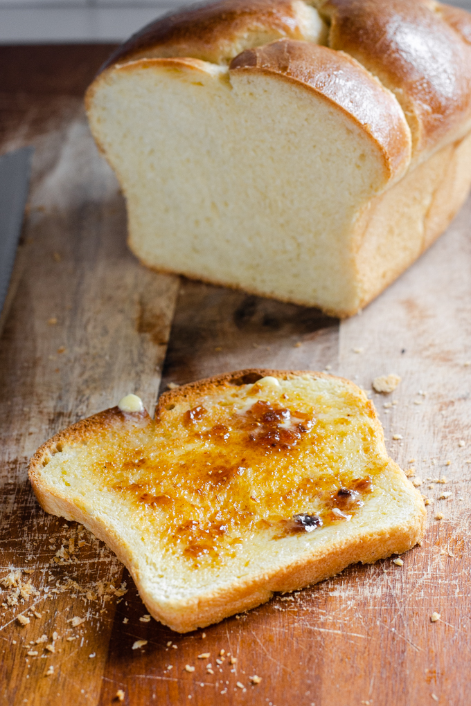 A toasted slice of sourdough brioche bread with melted butter and fig jam.