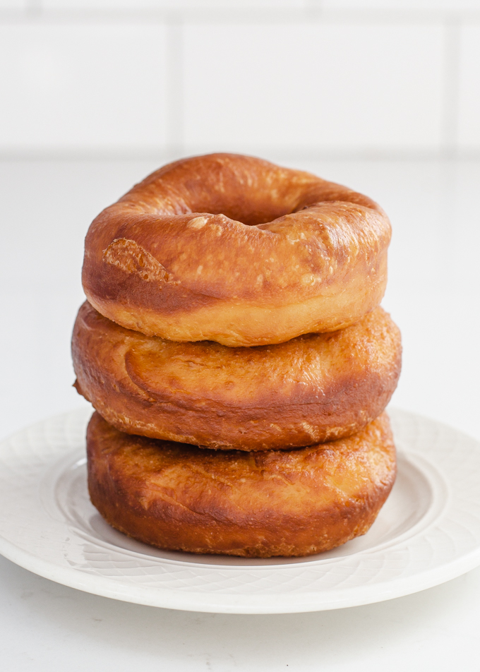 A stack of three donuts on a small plate made with my sourdough donut recipe.