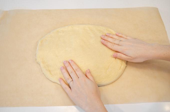 Patting the dough out on a piece of parchment paper.