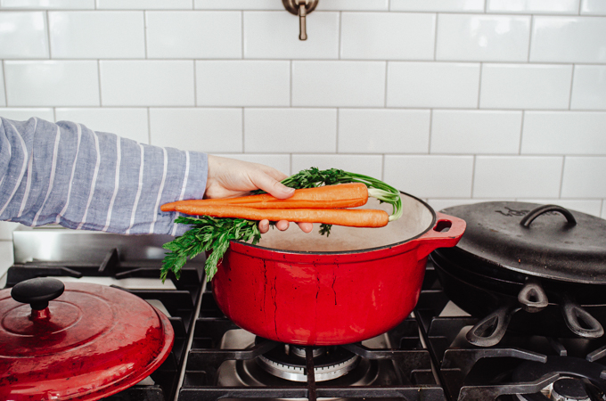 Adding carrots to a red Dutch oven.