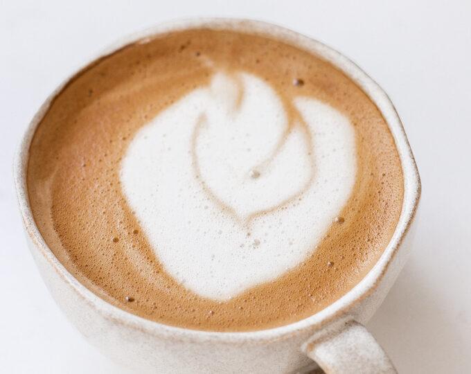 An oat milk latte in a stoneware mug.