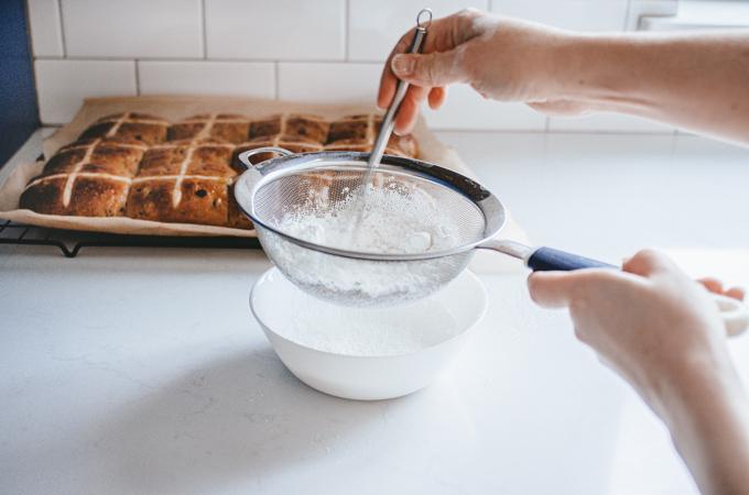 Sifting powdered sugar into a bowl.