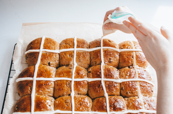 Piping the icing crosses onto the sourdough hot cross buns.