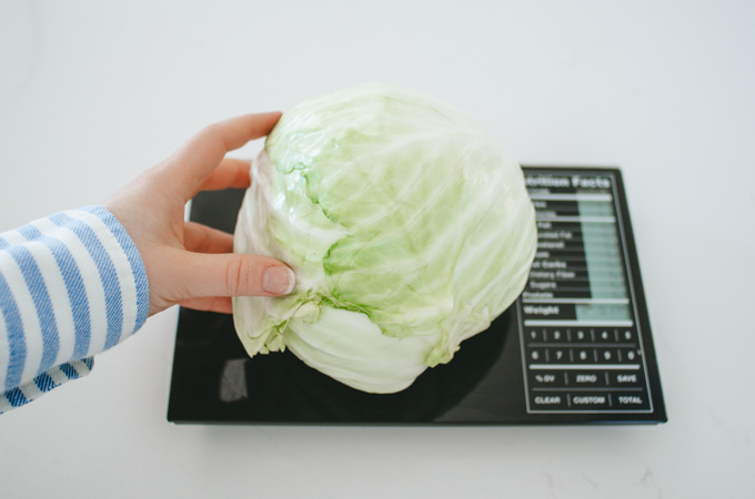 Weighing a head of cabbage for making homemade spicy sauerkraut.