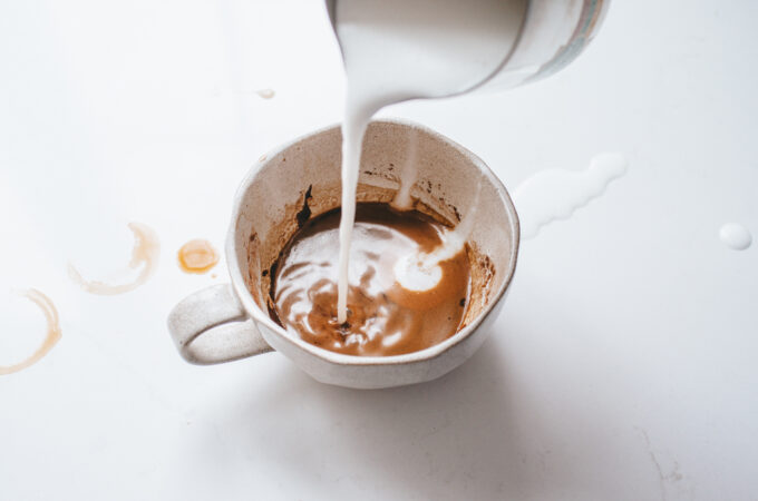 Pouring frothed milk into a cafe mocha.