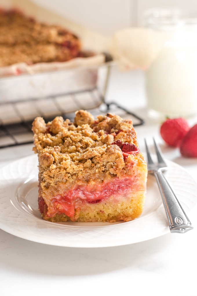 A slice of strawberry rhubarb crumb cake with strawberries and a glass of milk in the background.
