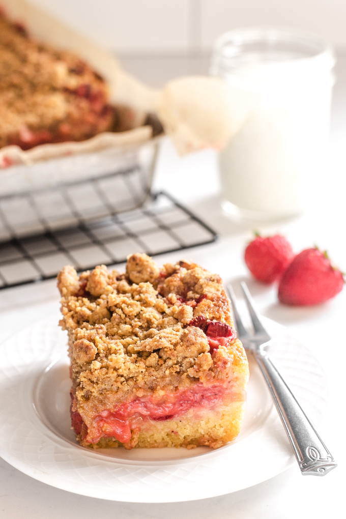 A slice of strawberry rhubarb cake with the cake pan in the background and a small dessert fork on the plate.