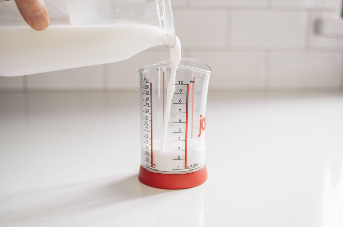 Pouring milk into a small measuring cup.